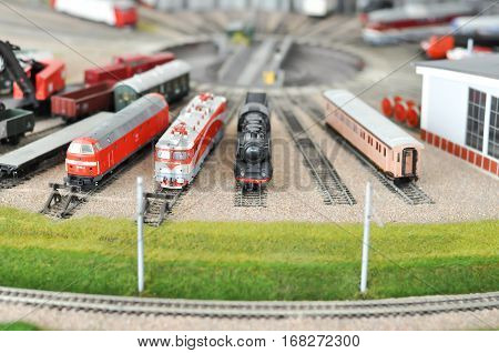 Railroad maquette with colorful trains and green grass fields