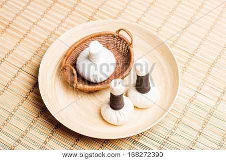 Massage bundles on a plate on bamboo mat. Spa, health, treatment, concept.