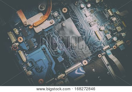 Disassembled laptop. Printed Circuit Board with many electrical components. Close up image. Technology and hardware electronic concept. Toned image