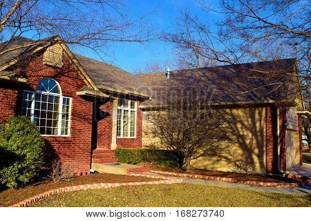 Middle class Midwest neighborhood with brick homes surrounded by deciduous trees