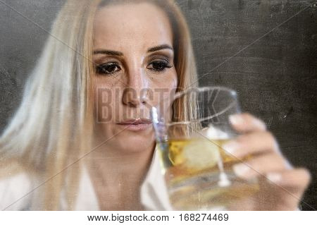 drunk woman alone in wasted and depressed face expression holding and looking thoughtful to scotch whiskey glass on dirty harsh background in alcohol abuse and alcoholic housewife concept