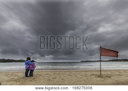 Girls observing the beach in one day with threat of imminent storm. The red flag indicates prohibited to bath.