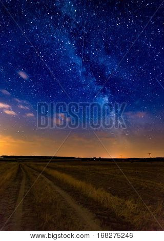 Milky Way Over Stubble Field And Rural Sandy Road