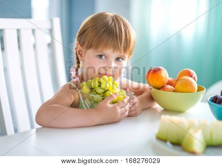 little pretty girl holding glass bowl with grapes at the table with other fruits