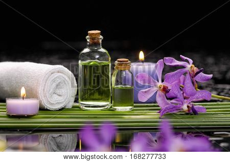 tranquil spa scene- pink orchid with candle ,oil green plant, towel,