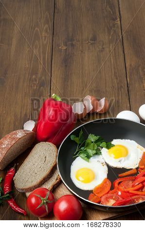 Delicious homemade omelette in vintage frypan with tomatoes, greens, bread and bell pepper on old rustic wooden background, top view. Healthy breakfast with fried egg on skillet pan. copy space