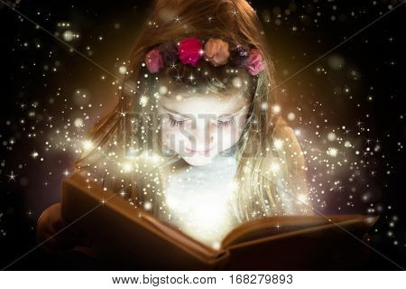 Little girl reading magic book, fantasy concept