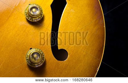 Jazz arch top guitar with a focus on the tone and volume knobs and f-hole