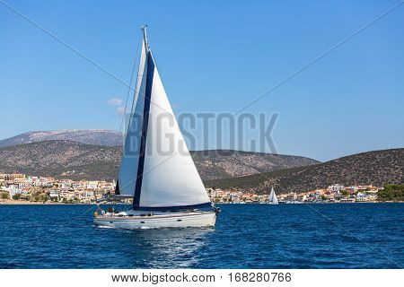 Sailing in the wind through the waves at Aegean Sea in Greece. Luxury yachts.