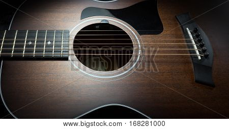 Acoustic guitar on a dark lit background
