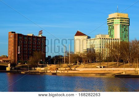 January 29, 2017 in Wichita, KS:  Downtown Wichita, KS skyline besides a pedestrian pathway alongside the Arkansas River where people can walk, cycle, and jog while admiring the river and skyline