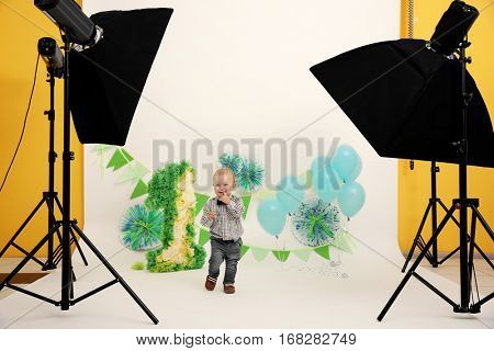 Cute baby boy on birthday decor background  at photo shooting