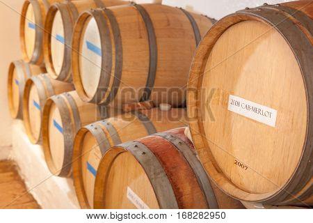 Several Various Wine Barrels Age Inside Cellar.