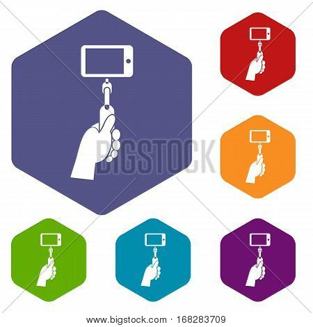 Hand holding a selfie stick with mobile phone icons set rhombus in different colors isolated on white background