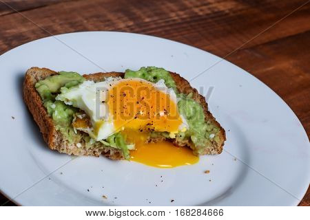Toast with avocado and egg on white plate