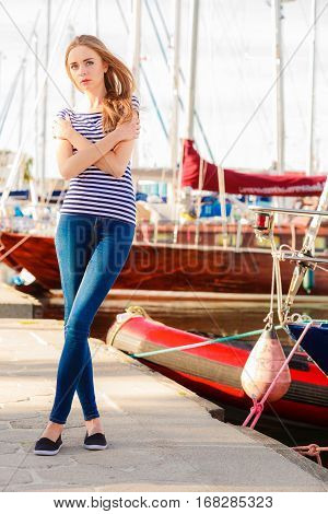 Travel tourism and people concept. Fashion blonde girl in marina against yachts in port