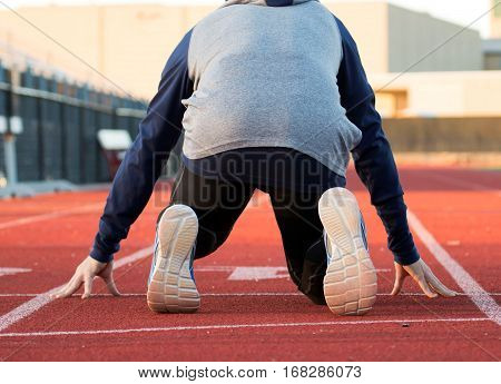 A sprinter training for track and field is in the on your mark position ready to run the 100 meter dash