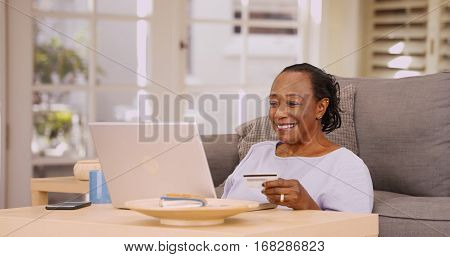 An Older Black Woman Pays Her Bills On Her Laptop