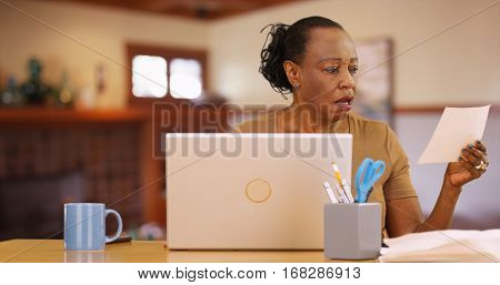 An Older Black Woman Sitting In Front Of Computer Shocked By Bill Payments