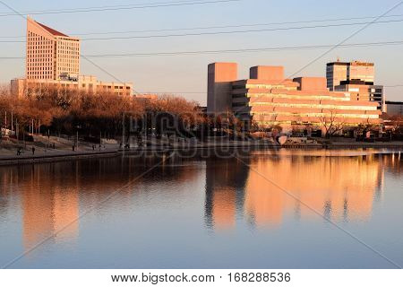 January 29, 2017 in Wichita, KS:  Highrise buildings alongside the Arkansas River reflecting on the water during sunset which is the Wichita Kansas Skyline where people can walk alongside the river while admiring the skyline taken in Downtown Wichita, KS