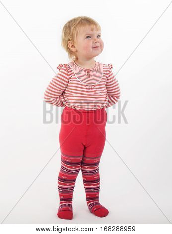 2 years old little girl smiling wearing red tights with red and white jacket