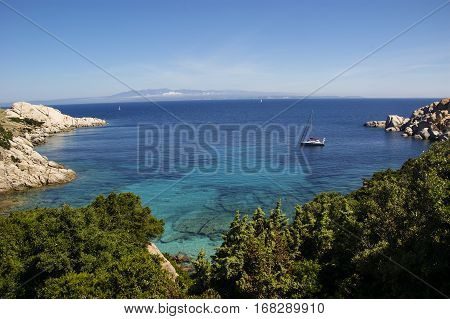 Small cove with turqoise blue water at Capo Testa in Sardinia boat and rocks and trees in foreground