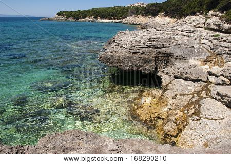 Rocks to the right in foreground with turquoise blue sea by a deserted shore at Capo Testa in Sardinia