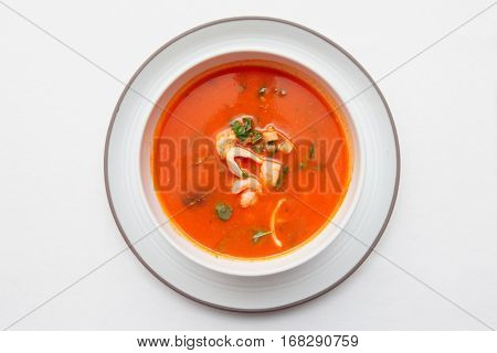 Tomato soup with fish and shellfish on white table cloth, shot from above