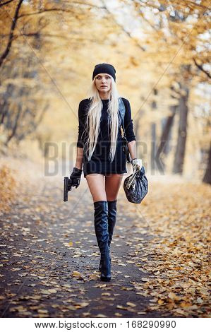 Sexy blonde girl with weapon is autumn park