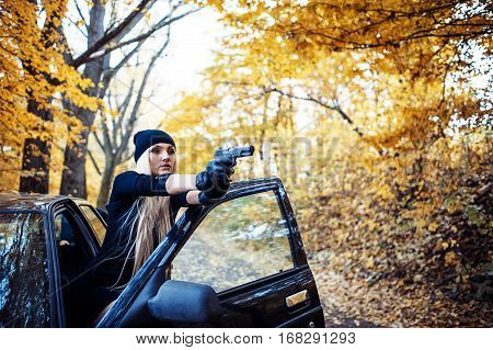 Sexy blonde girl with weapon near the black car