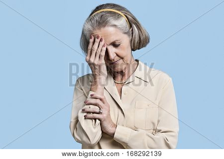 Senior woman suffering from headache against blue background