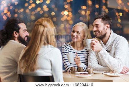 people, leisure, communication and friendship concept - happy friends meeting and drinking tea at cafe over holidays lights