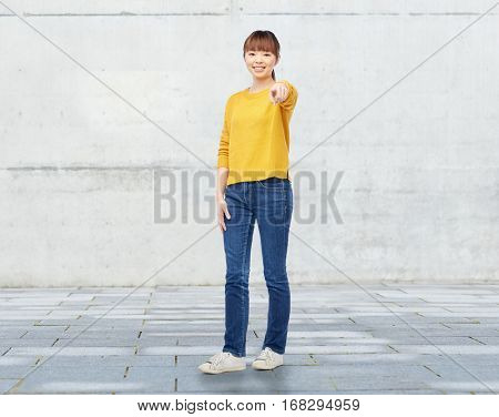 people, ethnicity, choice and gesture concept - happy asian young woman pointing finger on you over stone wall background