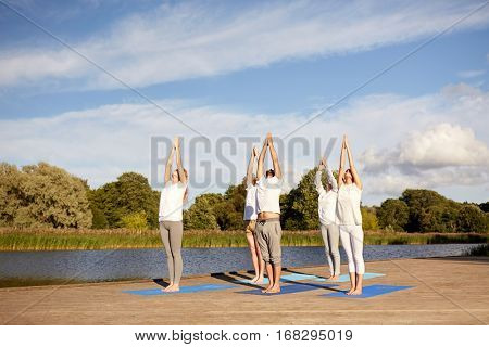 fitness, sport, yoga and healthy lifestyle concept - group of people making upward salute pose on river or lake berth