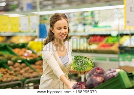 shopping, food, sale, consumerism and people concept - happy woman buying savoy at grocery store or supermarket