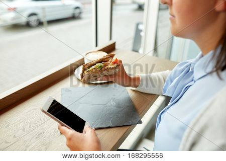 food, dinner, technology and people concept - woman with smartphone eating salmon panini sandwich with tomatoes and cheese at restaurant