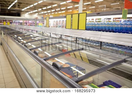 sale, shopping, consumerism and storage concept - freezers at grocery store