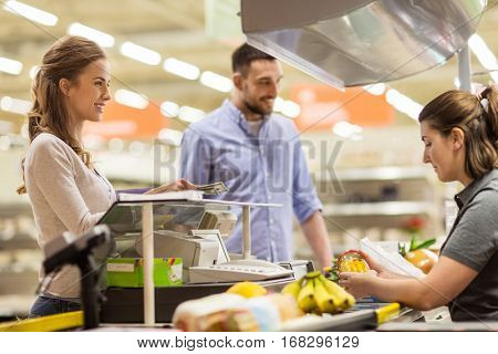 shopping, sale, consumerism and people concept - happy couple buying food at grocery store or supermarket cash register and paying cash money to cashier
