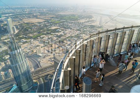 Dubai, UAE - January 06, 2017: Tourists meet sunrise at the observation deck on the 125 floor of Khalifa tower
