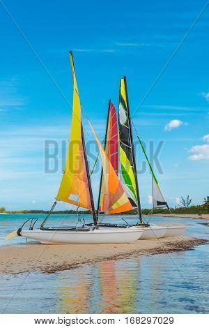 Small sailboats sitting on a sandbar in the caribbean.