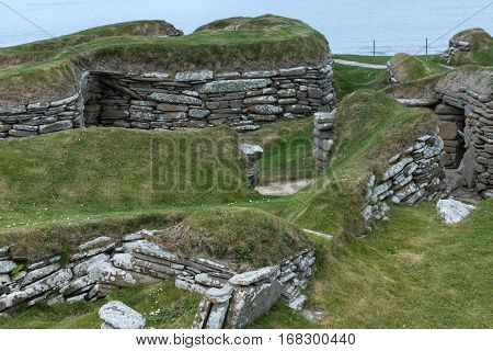 Orkneys Scotland - June 5 2012: Skara Brae Neolithic Settlement. Group of ruins and fundaments of dwelling set in the green dunes. Entrance to dwellings under ground. Gray and brown stones. Light blue Atlantic ocean in background.