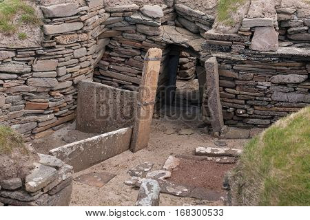 Orkneys Scotland - June 5 2012: Skara Brae Neolithic Settlement. Group of ruins and fundaments of dwelling set in the green dunes. Entrance to dwellings under ground. Gray and brown stones.
