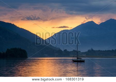 Sailing boat on Loch Leven in sunsetl Glencoe Scotland