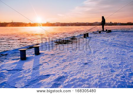 Fisherman standing on a pier at dawn sky background with sun rays and reflected in the sea water