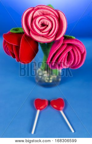 Shot of fabric red roses on a blue background with two red heart-shaped lollipops underneath the flowers.