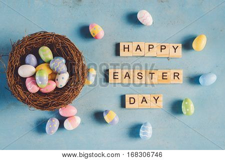 Colorful Easter Egg In The Nest And Wood Text Happy Easter Day On Blue Pastel Color Wood Background