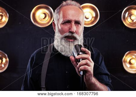 Close-up portrait of delighted stylish senior man in dark shirt and suspenders posing in front of a microphone displaying emotions. Studio shot of man posing over the background of blurred spotlights
