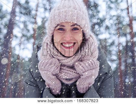 Extreme close-up of young attractive woman smiling at the camera. Winter forest atmosphere. Gorgeous woman with a vivacious smile looking at the camera