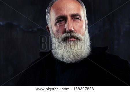 Studio portrait of bearded mature gentleman in formal clothes and black pullover isolated over background. Senior man with gray hair and beard. Studio shot against dark background