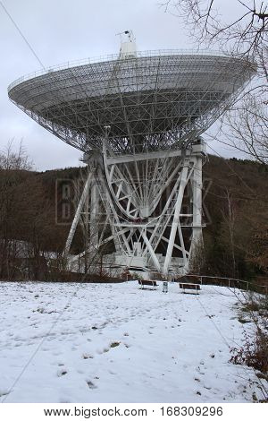 Radiotelcop Effelsberg largest fully mobile Radiotelcope of the earth in the Winter of 2017, in the background Secondary building and forest, in the foreground, snowy trail with railings .